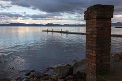 Una riva del lago al crepuscolo, con una vecchia colonna del mattone nella priorità alta Fotografie Stock Libere da Diritti