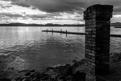 Una riva del lago, con una vecchia colonna del mattone nella priorità alta ed in una p Immagine Stock Libera da Diritti