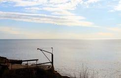 Una riva di mare adriatica e una vecchia barca (Montenegro, inverno) Immagini Stock