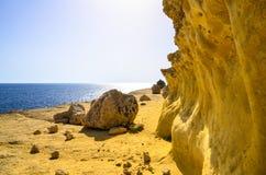 Una riva rocciosa dorata da un mare blu calmo, Malta Fotografia Stock