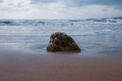 Una roca en la arena en la arena de una playa griega con agua de la turquesa imagen de archivo