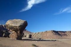 Una roca equilibrada con los acantilados bermellones en el fondo Imágenes de archivo libres de regalías
