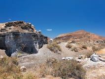 Una roccia scolpita ha scolpito tramite erosione di vento contro fondo di cielo blu profondo Ghiaia nera della lava Immagini Stock