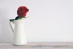 Una rosa roja en un florero blanco en un estante de madera blanco Fotografía de archivo