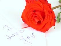 Una rosa roja y una carta de amor Fotos de archivo libres de regalías