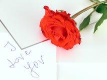Una rosa roja y una carta de amor Imágenes de archivo libres de regalías