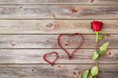 Una rosa rossa su fondo di legno con i cuori dal nastro valenti Fotografia Stock
