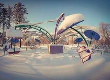 Una rotonda innevata nel parco della città immagine stock