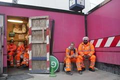 Una rotura durante trabajo Trabajadores en los trajes anaranjados que descansan sobre una pared rosada del fondo Foto de archivo