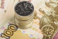 Una rublo contro lo sfondo delle fatture della cento-rublo Fotografia Stock Libera da Diritti