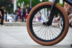 Una rueda de la bici de BMX contra el contexto de una calle borrosa con c Foto de archivo