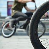Una rueda de la bici de BMX contra el contexto de una calle borrosa con c Fotos de archivo libres de regalías