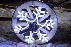 Una rueda que brilla intensamente, una guirnalda de la Navidad en la forma de un copo de nieve en una rueda de madera de un carro Fotos de archivo libres de regalías
