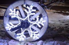 Una rueda que brilla intensamente, una guirnalda de la Navidad en la forma de un copo de nieve en una rueda de madera de un carro Imagen de archivo libre de regalías