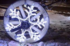 Una rueda que brilla intensamente, una guirnalda de la Navidad en la forma de un copo de nieve en una rueda de madera de un carro Foto de archivo libre de regalías