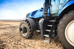 Una ruota da un trattore che funziona nella fine del campo su Il concetto di agricoltura Fotografia Stock