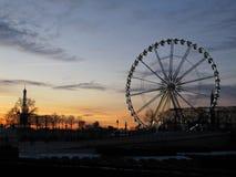Una ruota panoramica in un parco durante il tramonto immagini stock