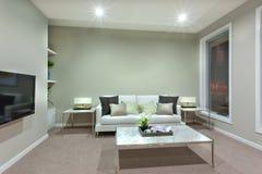 Una sala de estar con una peque?a tabla blanca y las almohadas en el sof? foto de archivo libre de regalías