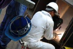 Una saldatura occupata dell'uomo di riparazione Immagine Stock Libera da Diritti