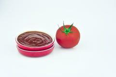 Una salsa y un tomate de la taza Foto de archivo libre de regalías