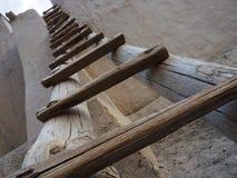 Una scala d'annata di legno da vecchio legno e ceppi vicino ad un'alta parete contro un fondo del cielo blu con le nuvole, parti  Fotografia Stock