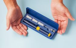 Una scatola con un insieme degli aghi, una fiala con una preparazione medica e una siringa per le iniezioni sottocutanee nel IVF Fotografia Stock Libera da Diritti