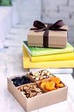 Una scatola dei dadi e dei frutti secchi e una pila di libri Fotografia Stock Libera da Diritti