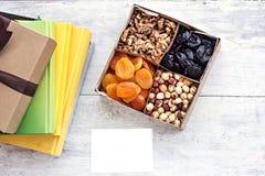 Una scatola dei dadi e dei frutti secchi e una pila di libri Fotografia Stock