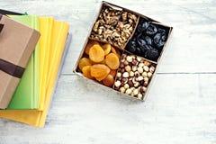 Una scatola dei dadi e dei frutti secchi e una pila di libri Immagini Stock