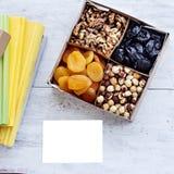 Una scatola dei dadi e dei frutti secchi e una pila di libri Immagini Stock Libere da Diritti