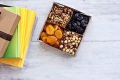 Una scatola dei dadi e dei frutti secchi e una pila di libri Immagine Stock Libera da Diritti