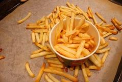 Una scatola di carta con le patate fritte che stanno su una teglia da forno Le patate fritte croccanti circonda il contenitore di immagine stock