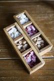 Una scatola di legno con lo zucchero lilla marrone bianco sta su una tavola di legno Pezzi di bianco marrone lilla colorato dello immagini stock libere da diritti