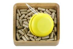Una scatola di legno in pieno delle medicine di erbe con il yo-yo giallo Immagini Stock Libere da Diritti