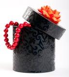 Una scatola nera legata con un arco arancione del nastro del raso Fotografia Stock Libera da Diritti
