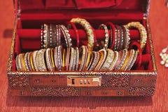 Una scatola rossa con la raccolta dei braccialetti o del braccialetto di scintillio per la sposa indiana Immagini Stock Libere da Diritti