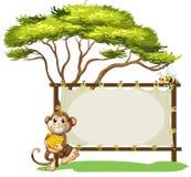 Una scimmia con una banana vicino al contrassegno vuoto Fotografia Stock Libera da Diritti