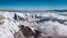Una scogliera della montagna coperta di neve, presa con il fuco fotografie stock
