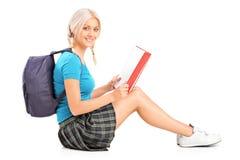Una scolara adolescente sorridente che legge un libro Immagine Stock