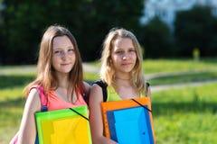 Una scolara di due ragazze Estate in natura Stanco di studio Nessuna forza da imparare più Nelle mani della cartella con fotografia stock libera da diritti