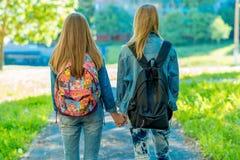 Una scolara di due ragazze Estate in natura Tenuta delle ragazze mani del ` s Vista posteriore I ritorni si dirigono dopo la scuo Immagine Stock Libera da Diritti