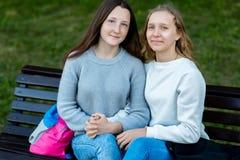 Una scolara di due ragazze di estate su un banco Accampandosi dopo la scuola Si tengono mani del ` s Il concetto di amicizia Fotografie Stock