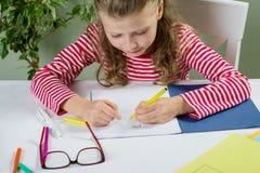 Una scolara minore con i vetri scrive qualcosa con la sua sinistra Fotografia Stock Libera da Diritti