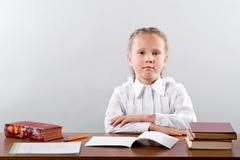 Una scolara piccola si siede ad uno scrittorio della scuola Immagine Stock