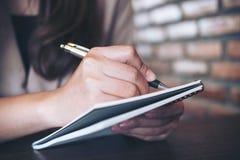 Una scrittura della donna di affari e prendere nota sul taccuino in ufficio fotografia stock libera da diritti