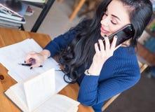 Una scrittura della studentessa in un taccuino mentre telefono di conversazione Immagine Stock Libera da Diritti