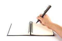 Una scrittura maschio della mano sul taccuino in bianco isolato Fotografia Stock Libera da Diritti