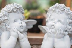 Una scultura bianca di due ragazzi del cupido fatta di cemento è nell'azione di pensiero e nello sguardo al cielo immagini stock