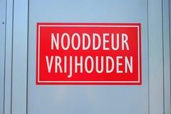 Una señal de peligro holandesa que dice 'guarda el claro de la salida de emergencia' Foto de archivo