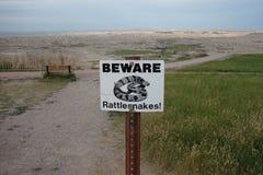 Una señal de peligro para los visitantes en los badlands imagenes de archivo